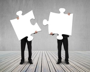 28580157 - businessmen holding two puzzles to connect on wooden floor